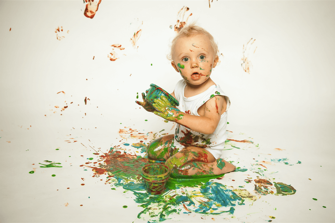 Baby covered in paint, sitting on the floor.