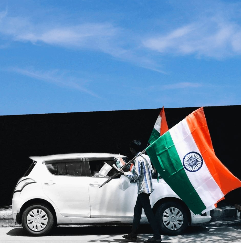 Man by Car Holding Flag of India.
