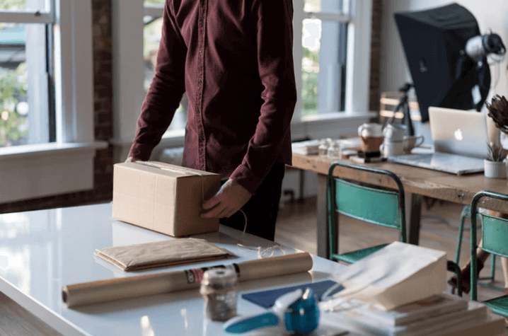 Man Packing a Box on a Desk.
