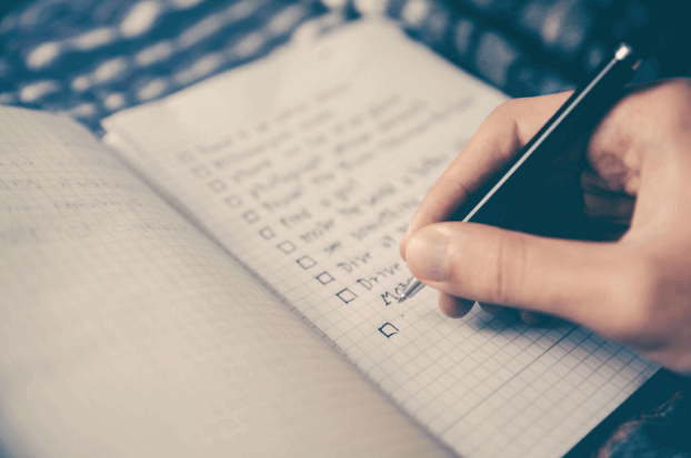 Woman holding a pen and ticking boxes on a checklist.