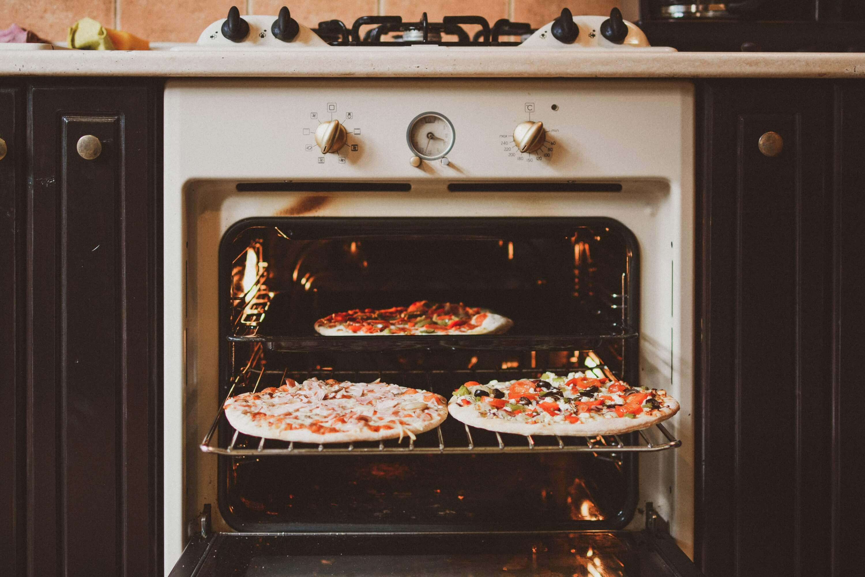 Open oven with pizzas.