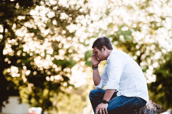 Man sitting on a bench and holding his head.