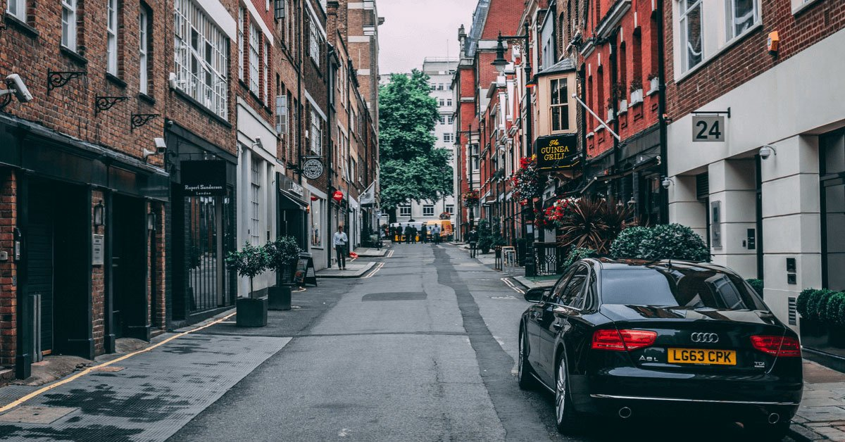 An old town street with a black car.