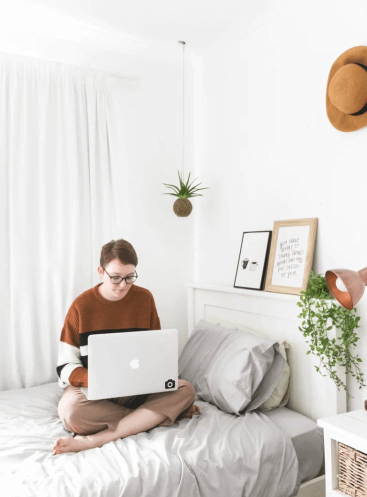 Young woman sitting on her bed with her laptop.